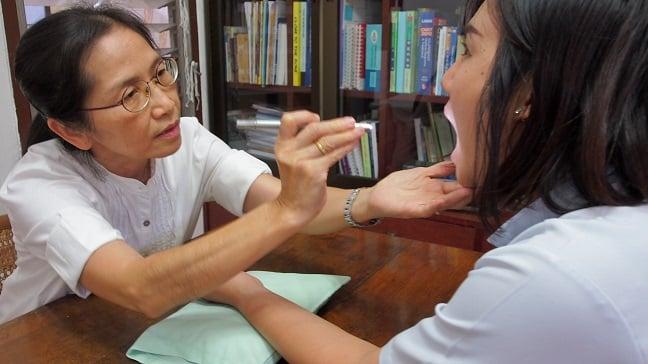 Dr.Rungrat checking tongue at Mungkala Clinic in Chiang Mai