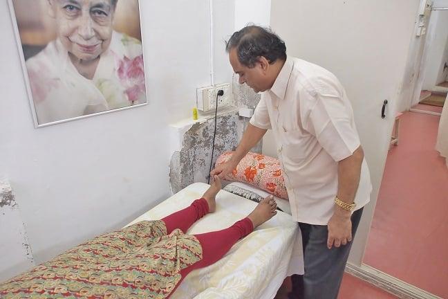 Mr.Sundararajan giving reflexology treatment to local lady